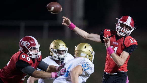 Greenville's Davis Beville (11) throws the ball as Daniel's defense approaches during the Red Raiders' 51-14 win at Sirrine Stadium Friday night. JOSH MORGAN/STAFF