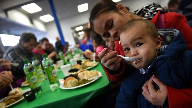 Phanh Brooks feeds her son, Jayden, during the annual Christmas Day lunch at the Reno-Sparks Gospel Mission in Reno on Friday. The Mission has served the area's homeless and needy since 1963.