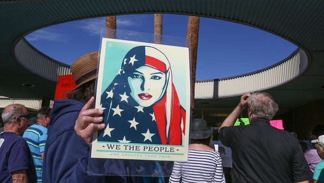 A man holds a poster of a woman wearing an American Flag scarf during a protest at Palm Springs City Hall on Jan. 31.
