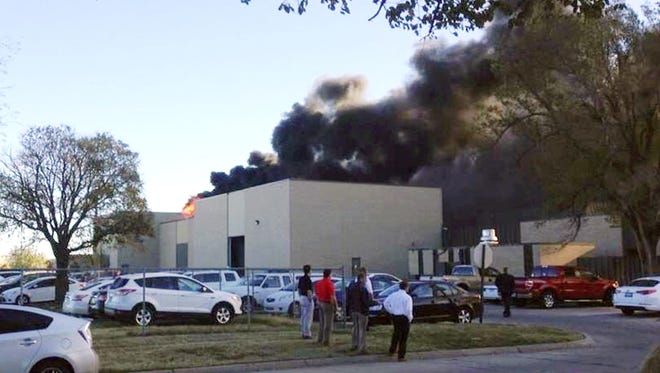 An image from video provided by KAKE News shows black smoke billowing from a building at Mid-Continent Airport, where officials say a plane crashed Thursday.