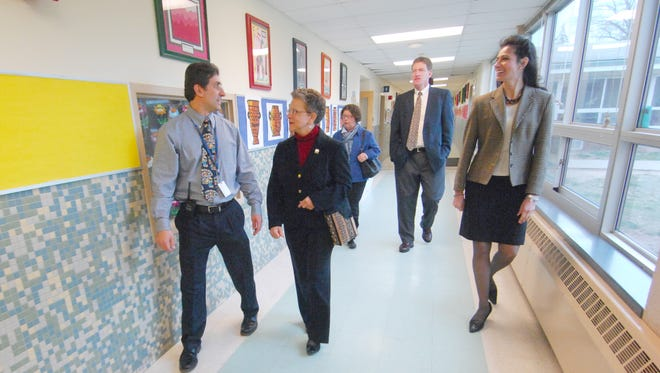 In this 2013 photo, Christine Burton, right, who assumes the role of superintendent of schools July 1, 2015, walks down the hallway during a visit to Hartshorn School with now former Millburn superintendent James Crisfield behind her. Assemblywoman Mila M. Jasey, second from left, is speaking with Hartshorn School Principal Kenneth Frattini.