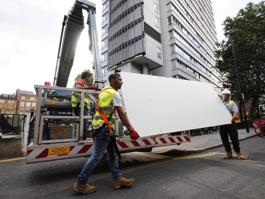 Workers remove panels of external cladding from the