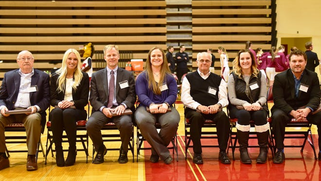 Among the the latest inductees to be enshrined into the Milford High Hall of Fame are (from left) former principal Eldon VanSpybrook (1967-73), Evia Prieditis (class of 2009), Jason Minock (1990), Sara Cupp (2010), Ron Berby (1960), Mellissa Bageris (2009) and Jason Amell (1999). The seven were recognized Friday during a ceremony between the Milford and Pinckney girls and boys basketball games.