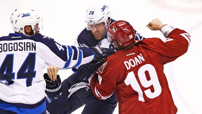 The Coyotes' Shane Doan throws a right at the chin of Winnipeg Jets' Blake Wheeler during a fight in the season opener on Thursday, Oct.9, 2014 at Gila River Arena in Glendale.