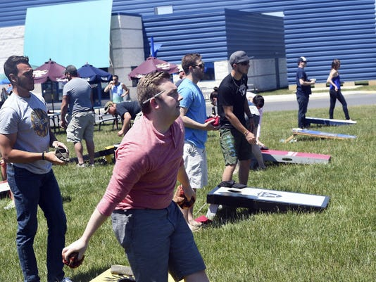 Chris Vene, left, and Zach Ferguson compete in a cornhole tournament Saturday at Good-Ta-Go in Chambersburg. Money raised from the event will support Relay for Life.