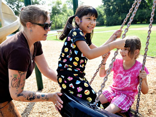 Evelyn Perez, center, 9, of Brooklyn, New York, is shown with her Fresh Air Fund host family Beth Jones, left, and Sally Materia, 8, right, on a quick stop at the park Wednesday after her arrival in York. This is Evelyn's third year to stay with Jones through the summer program.