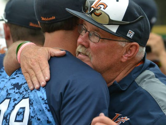 Louisiana College baseball coach Mike Byrnes (right) hugs outfielder Dylan Keller after a 12-5 win over Hardin-Simmons for the 300th win of his career with the Wildcats during a 2015 game.