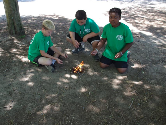 Participants in Camp YEY learn how to make a campfire.