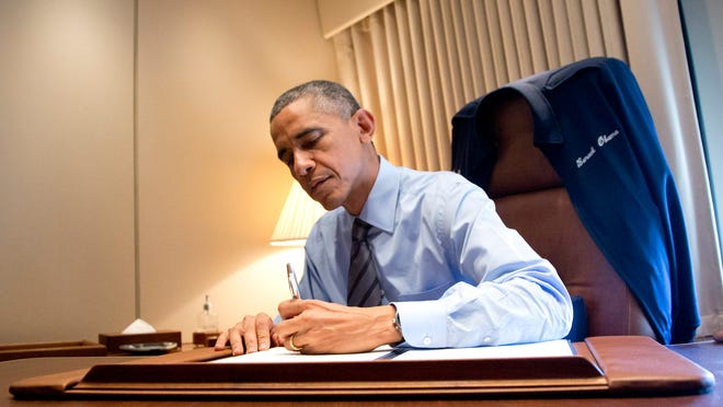President Barack Obama signs two presidential memoranda associated with his actions on immigration in his office on Air Force One on Nov. 21.