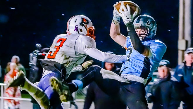 Tony Palmer (right) of Lansing Catholic grabs a pass in the Powers Catholic endzone over Powers Catholic defender Jaques Pougnet (left) midway through the 3rd quarter Friday in Holt.