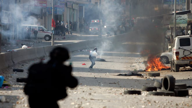Israeli troops fire teargas March 30, 2012, at protesters during clashes at the Kalandia checkpoint between Jerusalem and the West Bank city of Ramallah.
