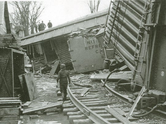 April 23, 1940: A young boy wanders through the wreckage of 25 cars in the middle of Waterbury as other onlookers peer down from their perch on top of tilted box cars.