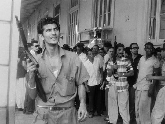 Two of Fidel Castro's 26th of July Movement soldiers wield guns in front of a crowd in Havana at the end of the Cuban Revolution in 1959. This photo was taken by Shorewood native and war photographer Dickey Chapelle.