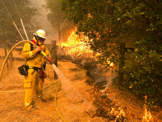 Napa County firefighter James George hoses down a fire