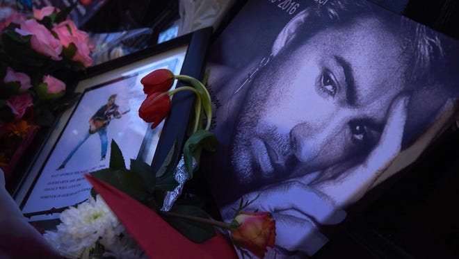 A message bearing a portrait of late British singer George Michael amid flowers, candles and messages left outside the singer's home in north London on Dec. 27, 2016.