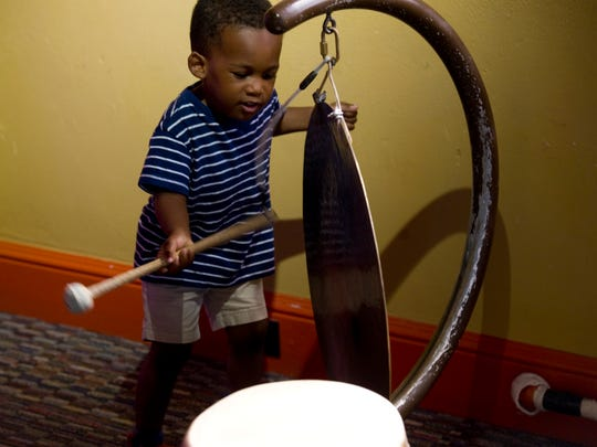 Xzavien Cannon, 3, of Evansville bangs a gong in the World Rhythms room at the Children's Museum of Evansville Wednesday afternoon.