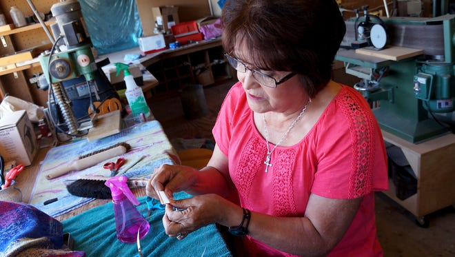 NMSU alumna Bernadette Apodaca wraps copper around a piece of stained glass. Apodaca and her family, along with several residents in Questa, N.M., are helping to restore St. Anthony's Catholic Church in Questa. Apodaca's family, the Raels, are originally from Questa.