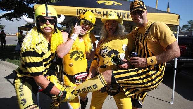 Hawkeye fans, from left, Morgan O'Conner, Jim Khana, Lance Neddler, and Eric Dolash pose for a photo while tailgating prior to the start of Iowa's game against Northern Iowa on Saturday in Iowa City. (Bryon Houlgrave/The Des Moines Register)