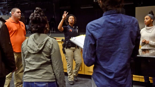 York City School police officer Britney Brooks, center, leads half a dozen students during a gospel choir rehearsal. Brooks, whose family moved to Virginia before she was old enough to attend William Penn Senior High School and join the school's gospel choir, revived the choir recently after several years of inactivity.