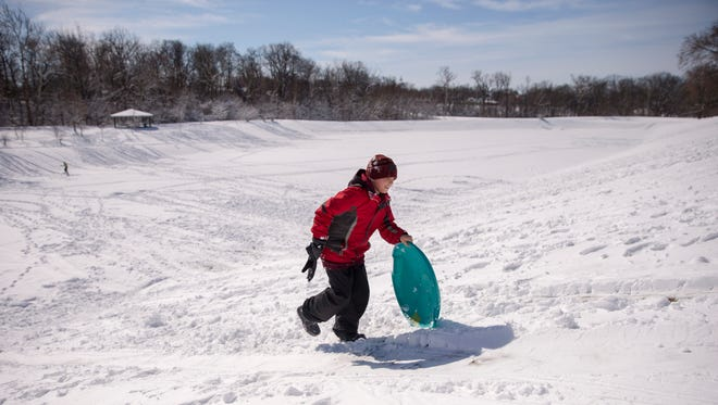 Ian Lovell, 11, Indianapolis, works his way up a hillside as the only sledder on a popular sledding run at Brookside Park, a day after 9-10 inches of snow dumped onto the area, Indianapolis, Sunday, March 25, 2018.