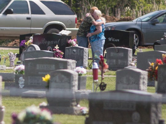 May 4, 2016: Mourners embrace after Kenneth Rhoden is laid to rest. The last of the eight Pike County murder victims' burials, was Wednesday at Mound Cemetery in Piketon.
