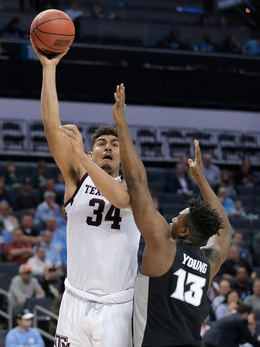 Texas A&M's Tyler Davis (34) shoots over Providence's Kalif Young (13) during the first half of a first-round game in the NCAA men's college basketball tournament in Charlotte, N.C., Friday, March 16, 2018. (AP Photo/Bob Leverone)