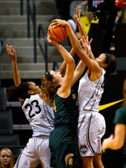 Michigan State's Lexi Gussert, center, is blocked and