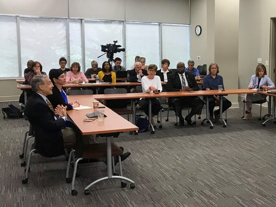 Mission Health President and CEO Ron Paulus, left, makes a point during a June 12 while local officials including Mayor Esther Manheimer, right, listen.