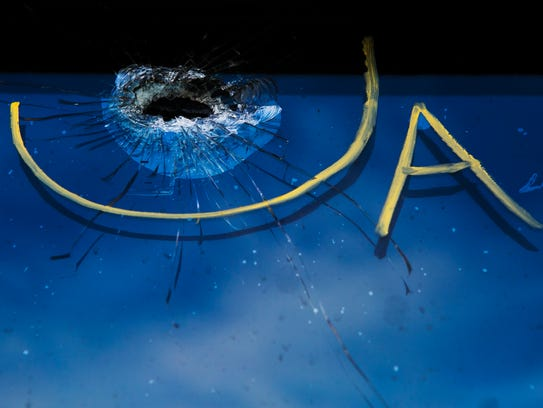 A bullet hole shattered a window at Creative Cuts and