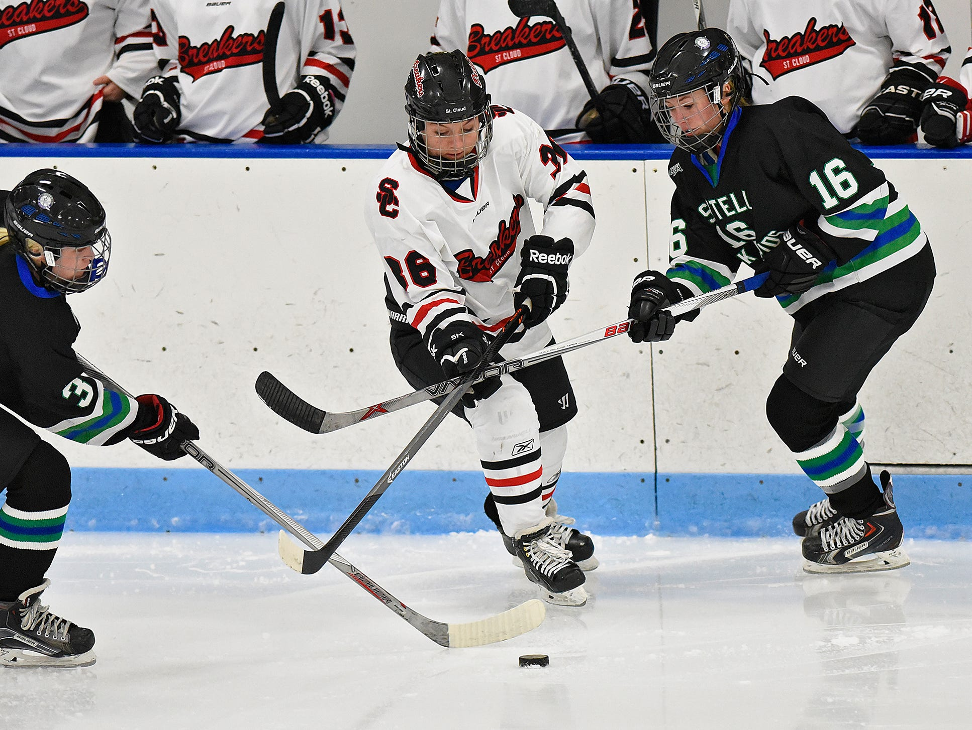 Megan Milroy of the Icebreakers tries to get past Bria Ferns (3) and Bre Hess (16) of the Storm'N Sabres 36 during the first period of Thursday's game at the MAC in St. Cloud.