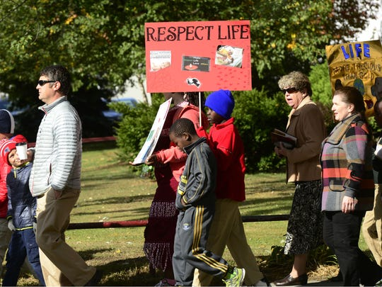 "Congregation members of the Catholic Cathedrals of Burlington march down Elmwood Avenue on Sunday prior to a mass for ""Respect Life Sunday."""