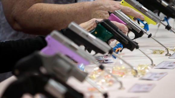 Attendees look over a pistol display at the National Rifle Association's annual convention April 25 in Indianapolis.