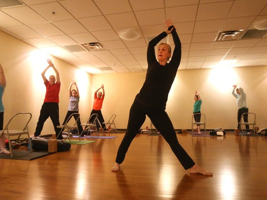 Yoga instructor Leslee Schenk Trzcinski leads a gentle yoga class at Midtown Athletic Club.