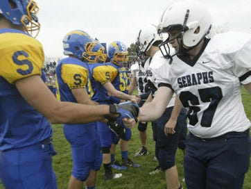 Spotswood and Mater Dei football players shake hands before a game.