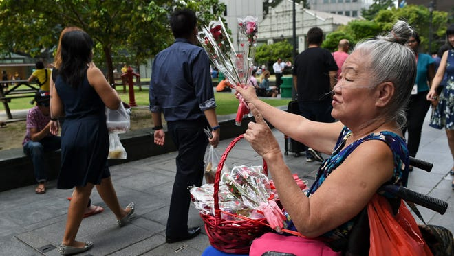 An elderly woman sells roses  in Singapore.