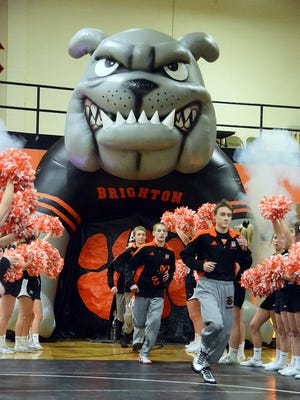 Brighton's wrestlers enter the gym for their season-opening dual through an inflatable Bulldog, flanked by the cheer team.