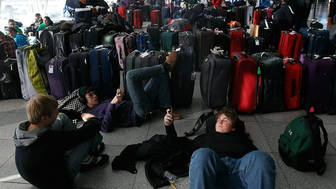 Travelers rest near dozens of suitcases while stranded at New York John F. Kennedy International Airport following a major blizzard on Dec. 27, 2010.