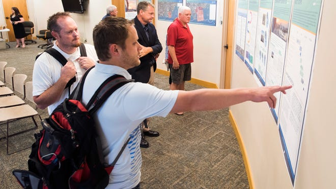 Matt Madson, center, and Tyson Creamer look over research on the Port of Pensacola during the Port Reinvestment Strategy Community Open House on Tuesday at City Hall.