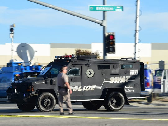 A SWAT police vehicle speeds past an officer on patrol
