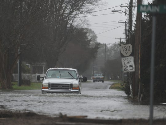A truck drives through flood water in Wachapreague,