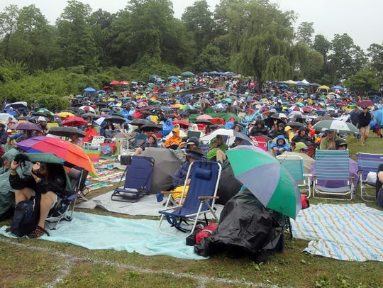 People listen to music from under the cover of umbrellas