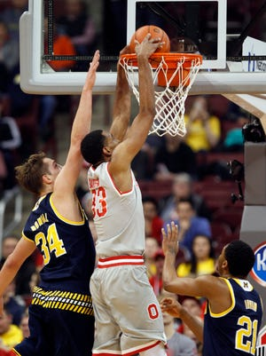 Ohio State's Keita Bates-Diop, center, dunks the ball against Michigan's Mark Donnal, left, and Zak Irvin during the first half of an NCAA college basketball game in Columbus, Ohio, Tuesday, Feb. 16, 2016. (AP Photo/Paul Vernon)