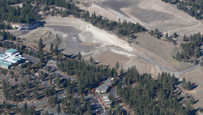 This 2013 aerial photo shows a pumice mine, center, adjacent to a former landfill, top, in Bend, Ore. Oregon State University is eyeing the 46-acre pumice mine as a possible location to expand its Cascades campus. (Rob Kerr/The Bulletin via AP) MANDATORY CREDIT