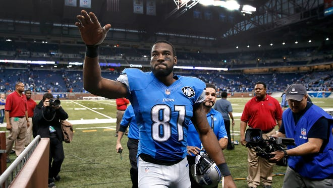 In this Nov. 9, 2014 photo, Detroit Lions wide receiver Calvin Johnson waves to fans after defeating the Miami Dolphins 20-16 in a NFL football game in Detroit.