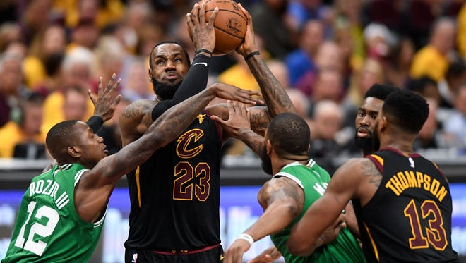 Cleveland Cavaliers forward LeBron James (23) attempts a layup against Boston Celtics guard Terry Rozier (12) and guard Marcus Smart (36) during the third quarter in game four of the Eastern conference finals of the 2018 NBA Playoffs at Quicken Loans Arena.