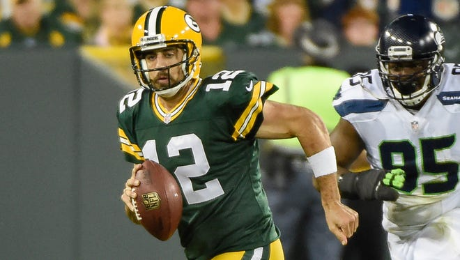 Green Bay Packers quarterback Aaron Rodgers (12) scrambles away from Seattle Seahawks defensive end Demarcus Dobbs (95) in the second quarter at Lambeau Field.