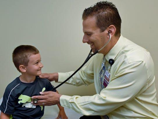 Dr. Michael Colli uses Scott Eshleman, 6, to show how