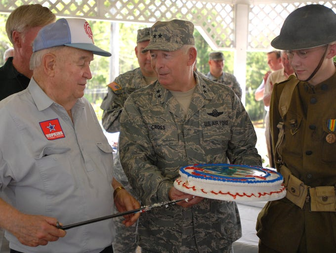 Maj. General Harold Cross, middle, holds a celebratory cake with World War I reenactor Travis Husted, right, looking on as Maj. Gen. Cohen Robinson, left, uses a 1917 bayonet to cut the cake during Camp Shelby's annual 2007 Retiree Day and 90th Anniversary commemoration.