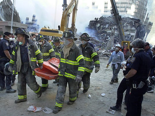 New York City firefighters remove a body from Ground Zero on Sept. 13, 2001.