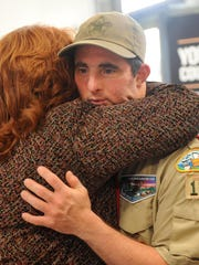 Rick Moloney receives a hug from Faline Rowland after Moloney delivered 1,200 pocket flags to the 179th Airlift Wing. Moloney, with help from his Troop 123 members, spent four months folding the flags for his Eagle Scout project.